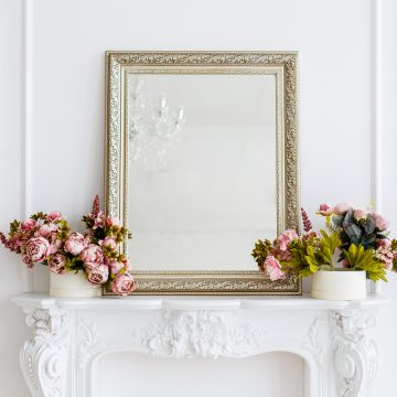 gold framed mirror on a white fireplace mantel with flowers on either side