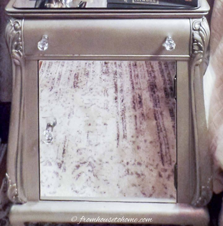 The front of the nightstand with the mirror and the crystal knobs