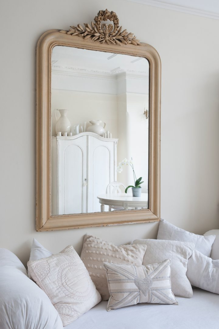 Wood mirror hung above a day bed with lots of cushions