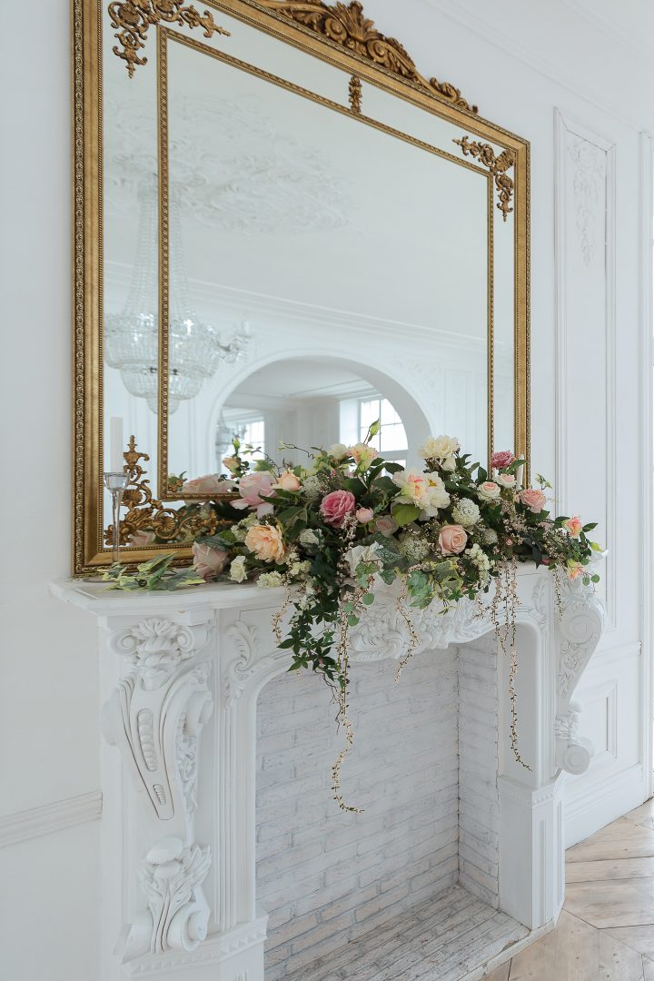 Large gold-framed mirror above a fireplace mantel with a flower garland