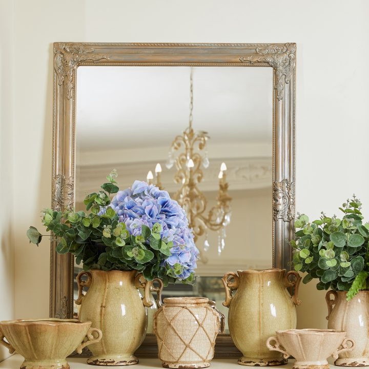 Ceramic pots on a mantel surrounding a gold-framed mirror that reflects a chandelier