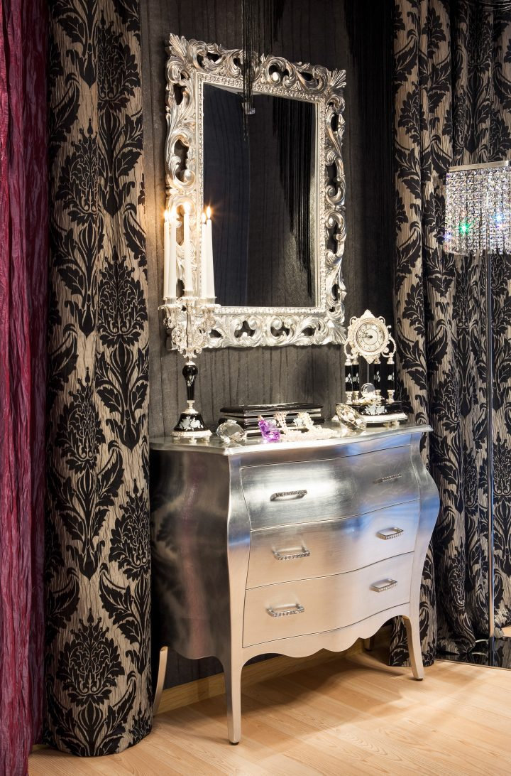 Ornate silver-framed mirror above a silver chest in a black room