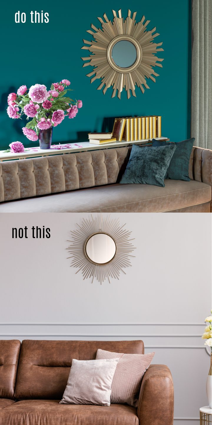 Round mirror hung at the correct height above a sofa with books and flowers vs a round mirror that is too small and hung too high above the sofa