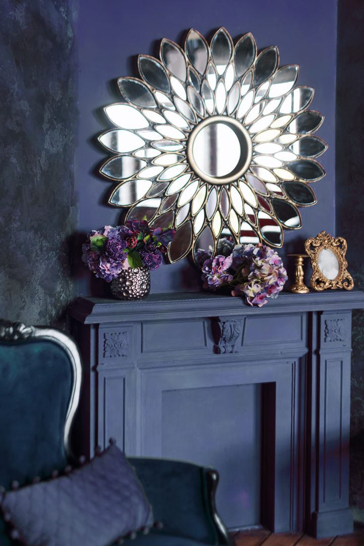 Flower shaped mirror above a fireplace mantel in a dark blue room