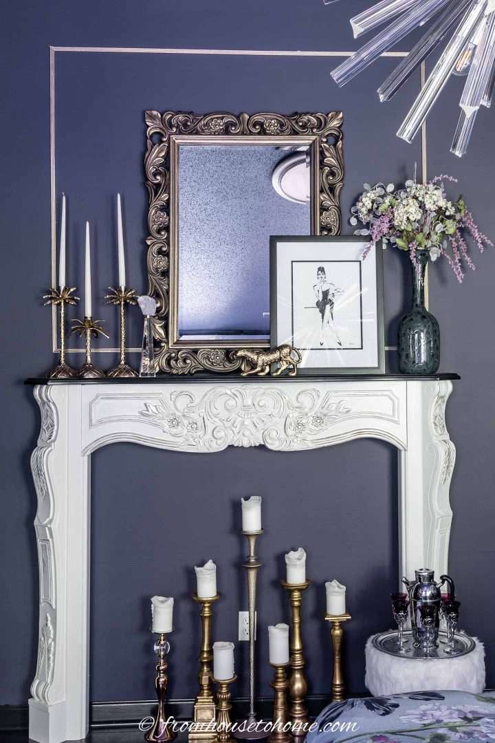 Gold mirror with a picture, candles and a dried flower arrangement on a fireplace mantel
