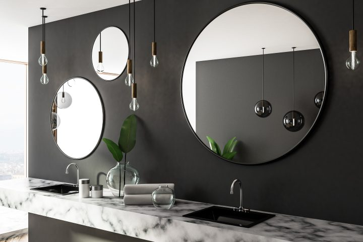 Round mirrors hung in an asymmetrical grouping in a bathroom