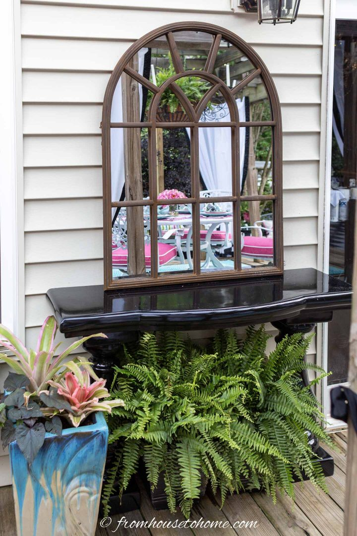 Outdoor garden mirror on a console table on the deck