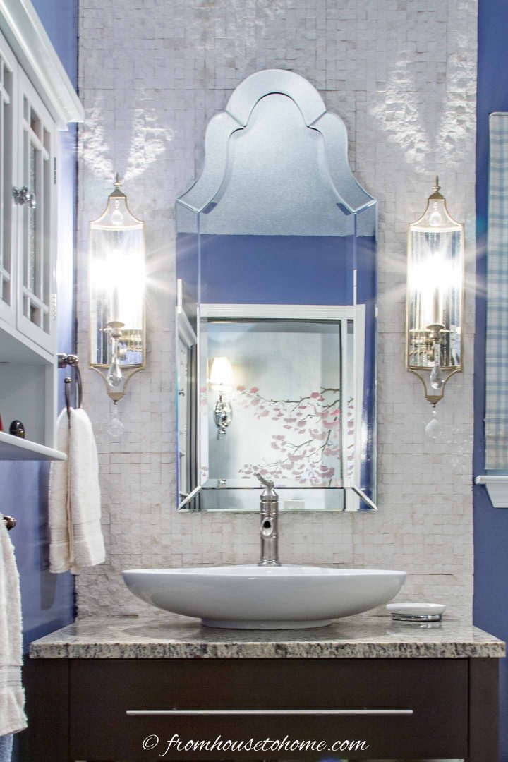 Venetian mirror hung between two wall sconces above a bathroom sink