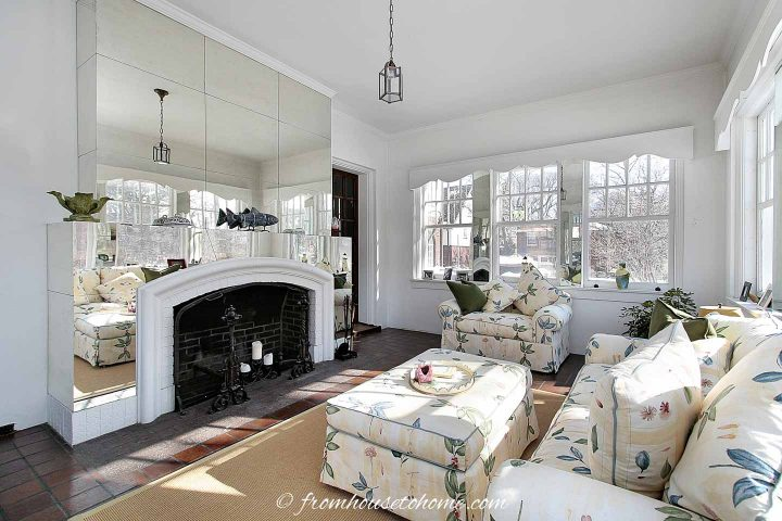 Mirrored fireplace surround in a living room with lots of windows
