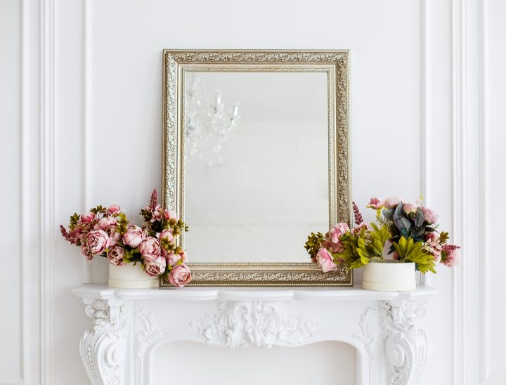 Gold mirror and pink flowers on a white fireplace mantel ©Olga Mishyna - stock.adobe.com