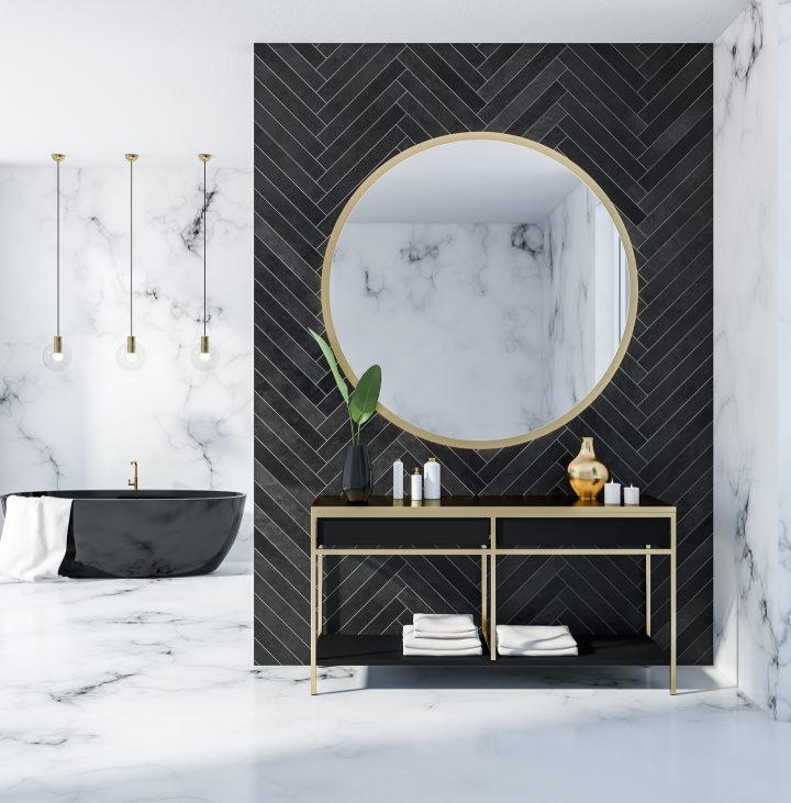 Black bathroom wall with a large round mirror