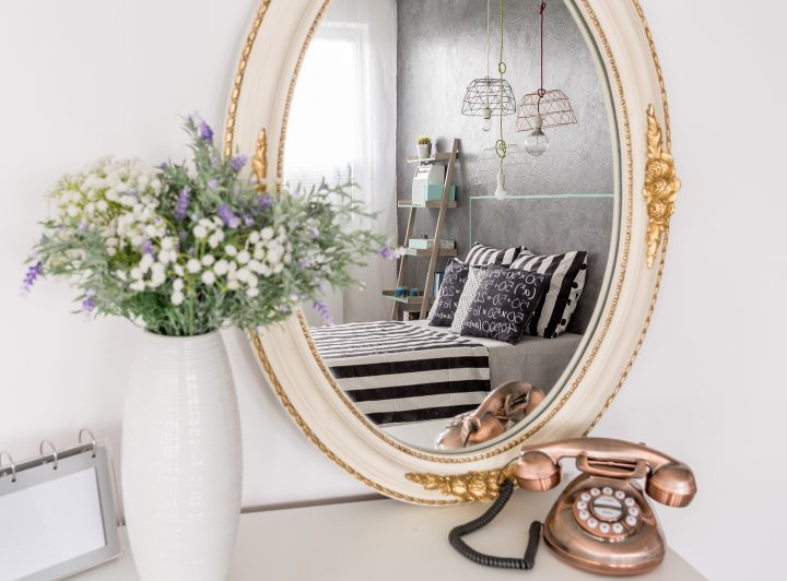 Bed reflected in an oval mirror on the wall