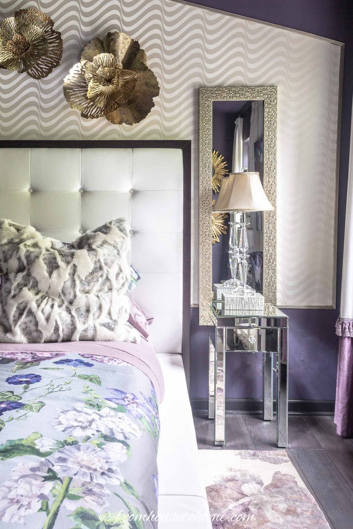 Bedroom with a tall mirror behind the nightstand