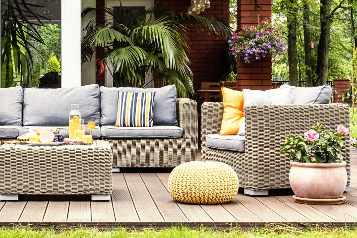 Outdoor living room with wicker furniture and blue and yellow cushions