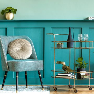 2021 home decor trends: Teal chair and wall with brass bar cart