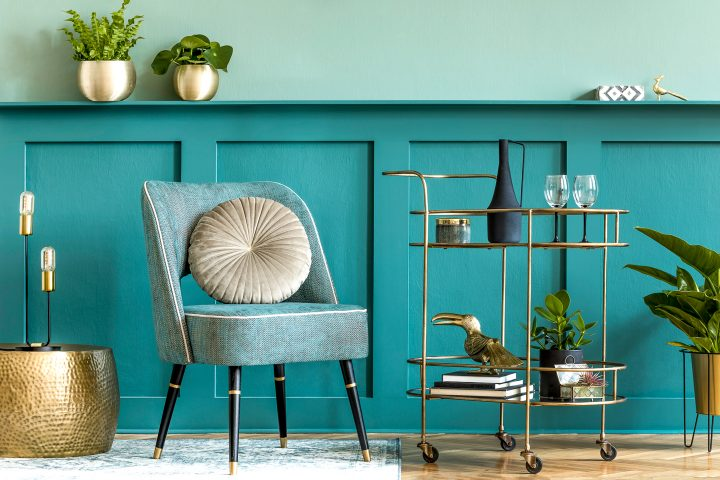 Living room with teal walls and brass bar cart and flower pots