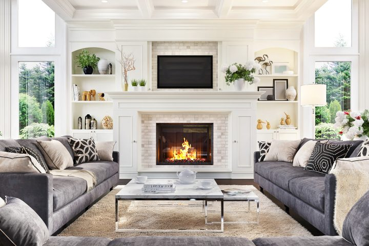 Living room with modern gray sofas and traditional white fireplace decor