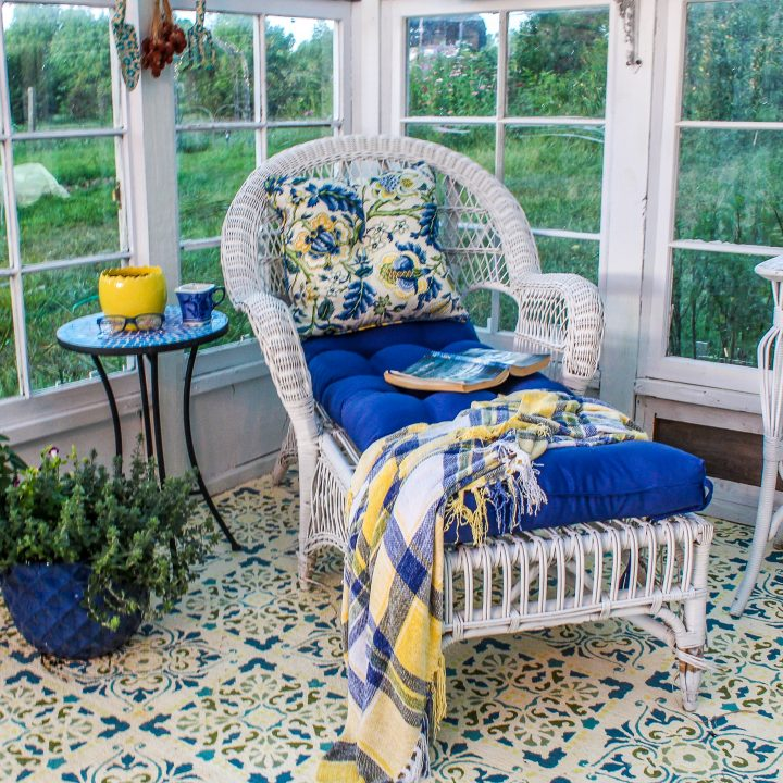 White wicker chair with blue and yellow cushions in a sunroom
