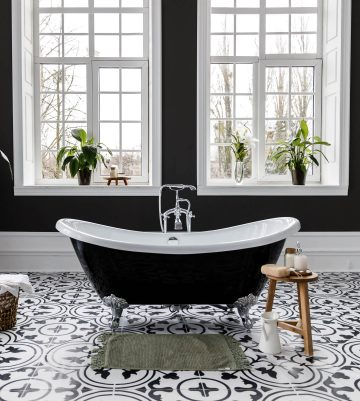 bathroom with black clawfoot tub and black and white floor tiles