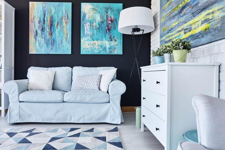 Grandes pinturas em turquesa sobre um sofá azul claro