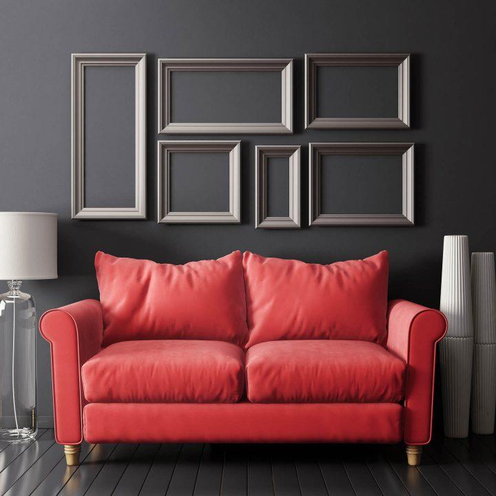 Uma parede de molduras vazias acima de um sofá vermelho