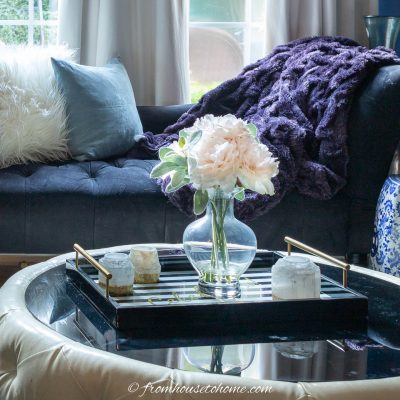 Round coffee table with some candles and faux flowers on a tray