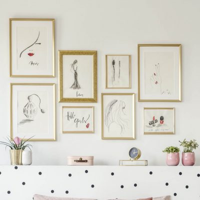 Gallery wall of drawings with gold frames