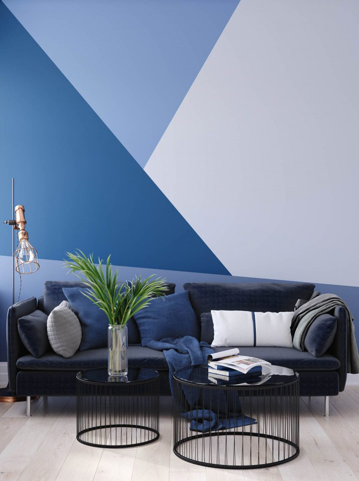 Living room with a blue triangle pattern painted on the wall behind the couch