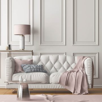 off white sofa with pale pink accessories in front of a neutral colored wall