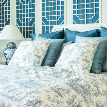 bedroom with blue and white lattice panels on the wall and blue and white toile bedding