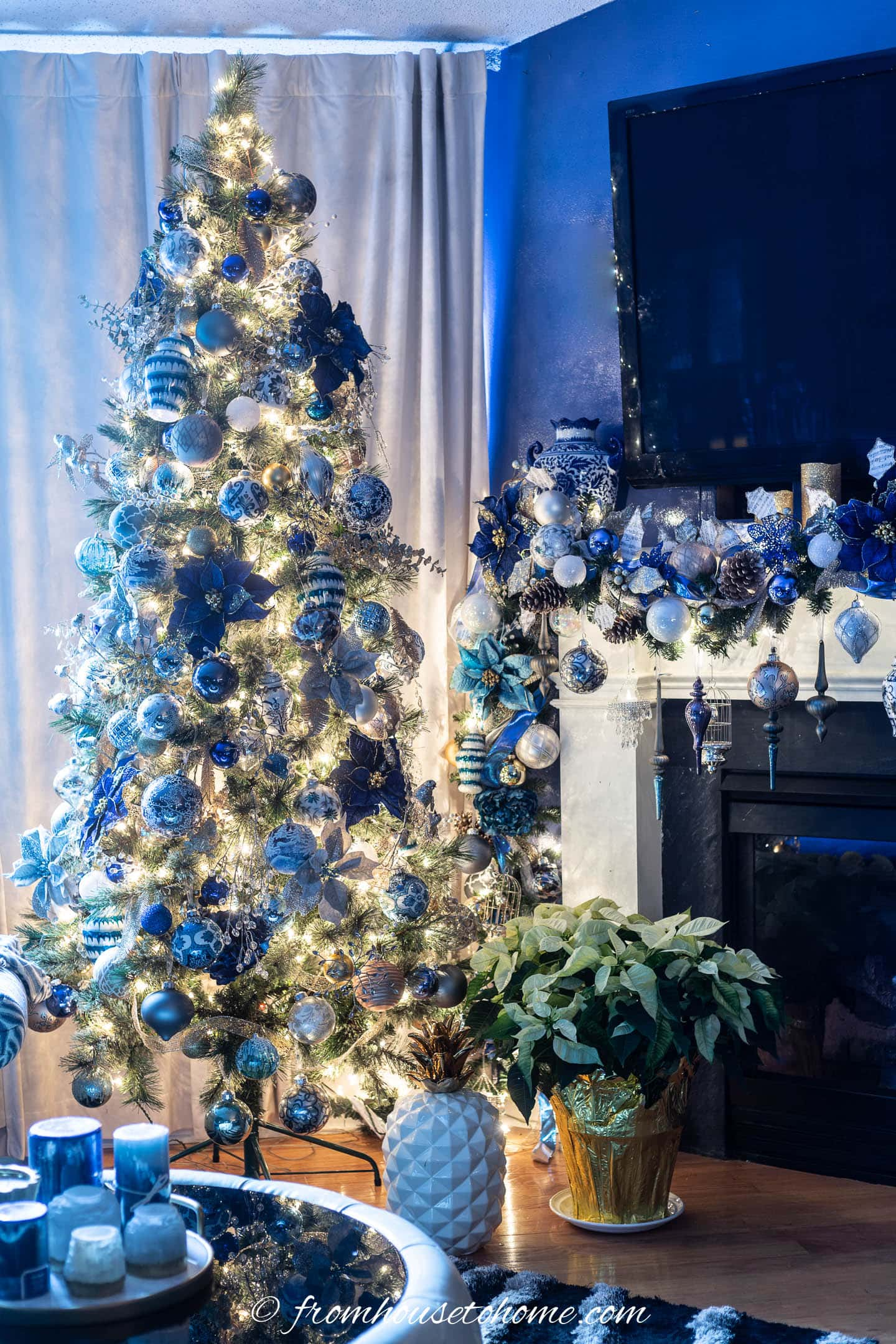 A TV over a fireplace mantel decorated with a garland and Christmas ornaments beside a blue and white Christmas tree